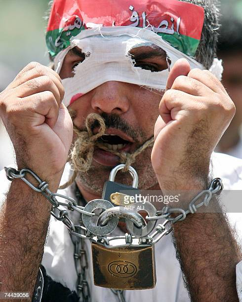 Pakistani opposition party activist binds his mouth and hands with locks while he marches during an anti-Musharraf protest rally in Lahore, 07 June...