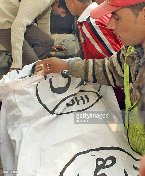 A Pakistani rescue worker covers the face of boy Umar Farooq who was killed by kite cord during the Basant or kite flying festival in Lahore 25...