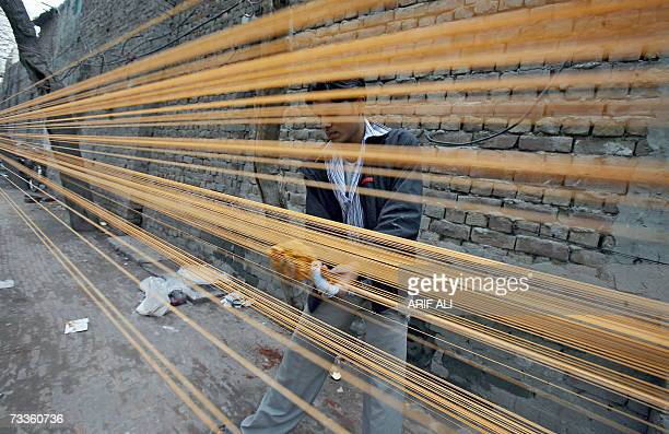 A Pakistani youth prepares special treated thread used to fly kites at a roadside stall in Lahore 18 February 2007 on the eve of The Basant Festival...