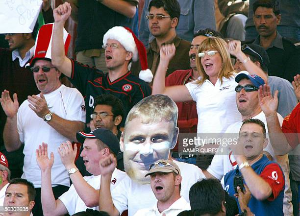 A supporter of England's cricket team holds up a cutout portrait of cricketer Andrew Flintoff as fans sing during the second day of the third and...