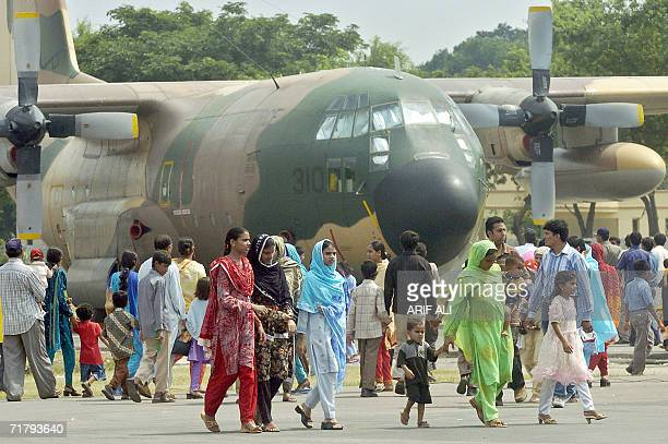 CORRECTION Pakistani visitors gather around an Air Force transport C130 plane during a military display to celebrate the country's Defence Day in...