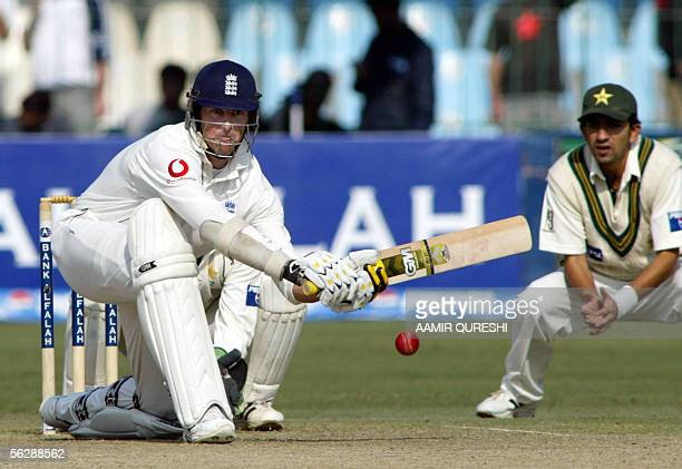 England batsman Marcus Trescothick eyes a ball as he plays a stroke against Pakistani spinner Shoaib Malin as Hassan Raza looks on during the first...