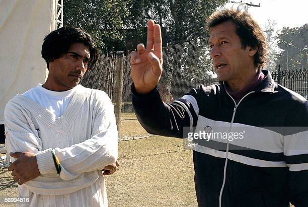 In this file photograph taken 06 January 2006, former Pakistani cricketer Imran Khan gives bowlling tips to current Pakistani fast bowler Mohammad...