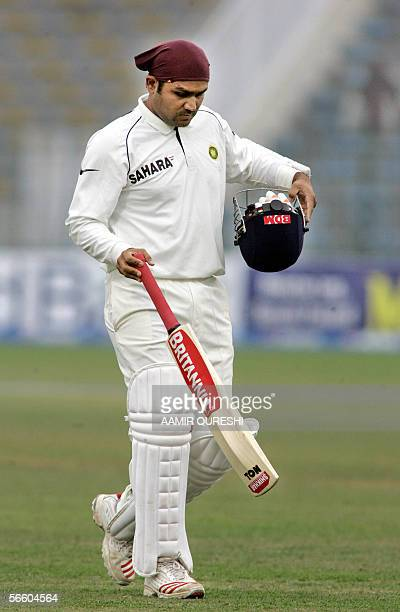 Indian batsman Virender Sehwag walks back to the pavillion after his dismissal by Pakistani bowler Naved-ul-Hasan for 254 runs during the fifth and...