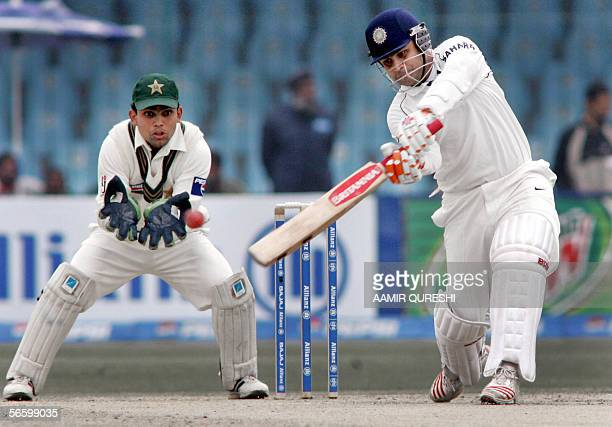 Indian batsman Virendra Sehwag makes a century as he hits a boundary off Pakistani spinner Danish Kaneria as wicket-keeper Kamran Akmal looks on...
