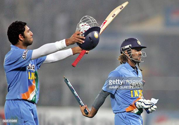 Indian crIcketer Yuvraj Singh waves his bat as teammate Mahendra Singh Dhoni waves a wicket after their victory over Pakistan during the third One...