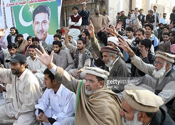 Pakistani activists of the hardline Muttahida MajliseAmal an alliance of six fundamentalist parties sit beside a portrait of Abdul Qadeer Khan the...