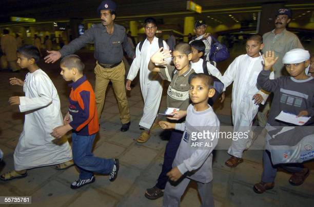Pakistani children who were smuggled and used as camel race jockeys in the United Arab Emirates are escorted by security personnel upon their arrival...