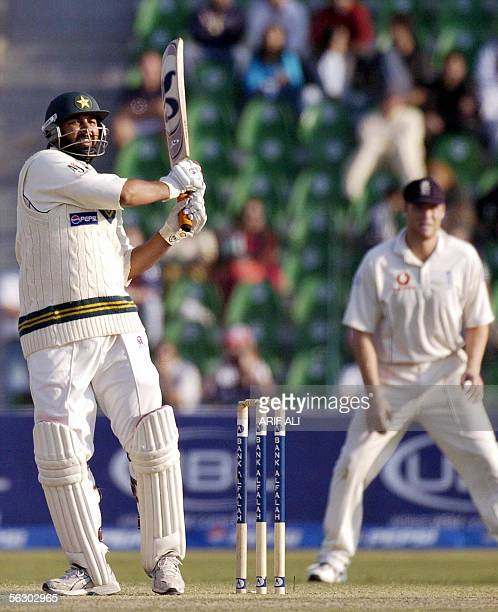 Pakistani cricket captain InzamamulHaq watches the ball after playing a stroke as England cricketer Andrew Flintoff looks on during the second day of...