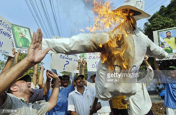 Pakistani protesters shout slogans as they carry a burning effigy of Australian cricket umpire Darrell Hair during a protest in Lahore 23 August 2006...