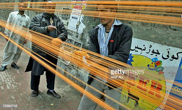 Pakistani vendors prepare special treated thread used to fly kites at a roadside stall in Lahore 18 February 2007 on the eve of The Basant Festival...
