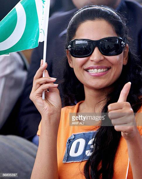 Popular Pakistani actress Meera shows a thumb up as she holds a country flag during the third One Day International match between Pakistan and India...