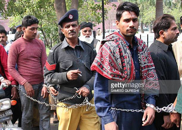 TO GO WITH AFPLIFESTYLEPAKISTANKITEISLAM This picture taken 26 February 2007shows a Pakistan policeman escorts handcuffed men at a court in Lahore...