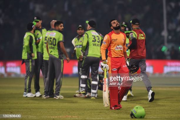Lahore Qalandars celebrates the wicket of Islamabad United Shadab Khan  walks back to the pavilion during the Pakistan Super League T20 cricket match...