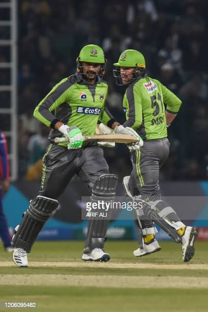 Lahore Qalandars's Ben Dunk and Sohail Akhtar run between the wicket during the Pakistan Super League T20 cricket match between Karachi Kings and...