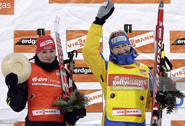 Sweden's Anna Carin Olofsson waves to supporters next to winner of the IBU Womens' 15 km Biathlon Andrea Henkel of Germany 28 February 2007 in Lahti...
