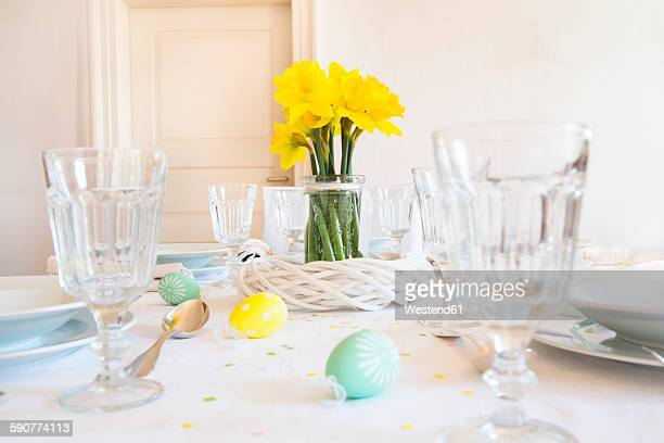 Laid Easter table with bunch of daffodils