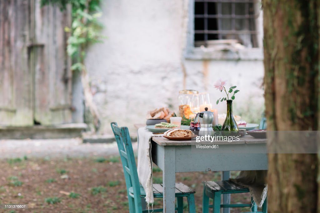 Laid garden table with candles next to a cottage : Stock Photo