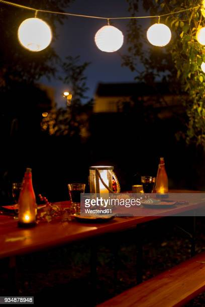 laid table in garden at night - lantern stock photos and pictures