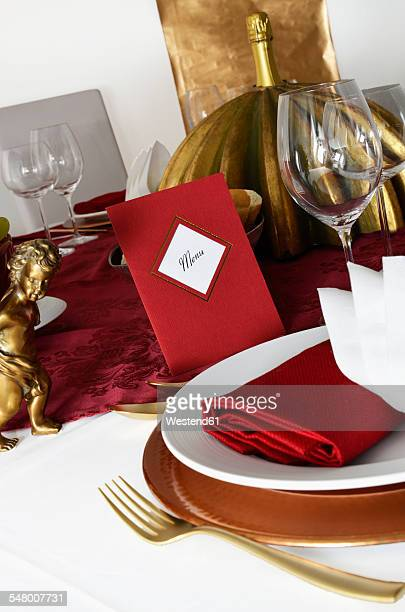 Laid table, red menu card, red and golden place setting