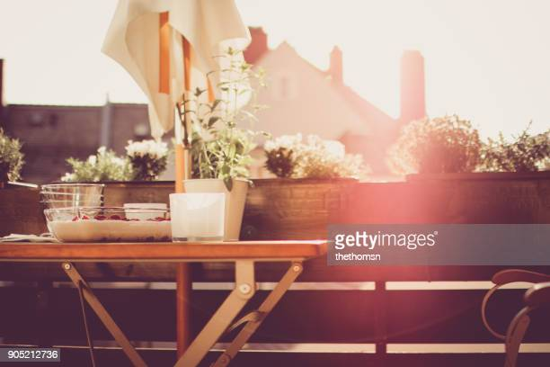 laid table with dessert on balcony during sunset - balkon stock-fotos und bilder