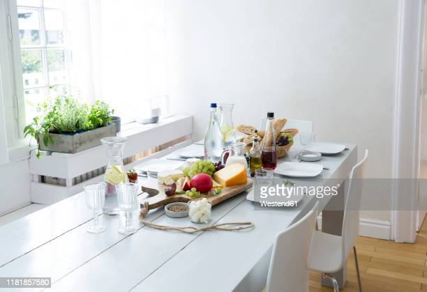 laid table with fruit, cheese and bread - speisezimmer stock-fotos und bilder