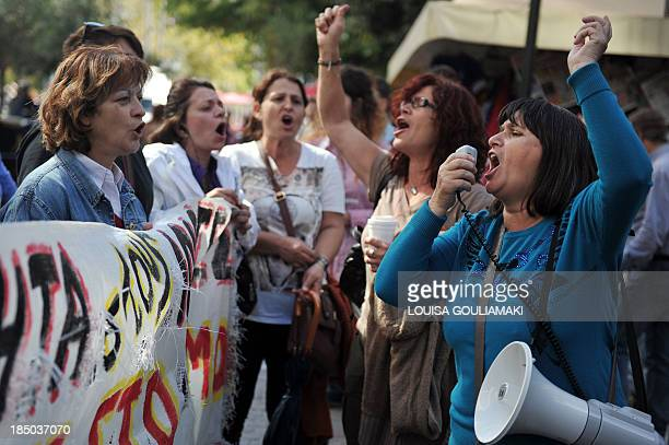 Laidoff cleaning staff members of the Greek finance ministry shout slogans during a protest against job cuts outside the ministry in central Athens...