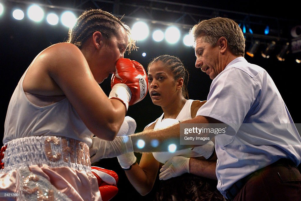 Laila Ali and Christy Martin square off with Referee Fred Steinwinder on August 23, 2003 at the Mississippi Coast Coliseum in Biloxi, Mississippi. Ali would knock out Martin in the fourth round.
