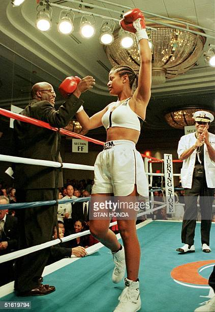 Laila Ali daughter of boxing great Muhammad Ali celebrates her victory over April Fowler of Michigan City Indiana with an official at ringside 08...