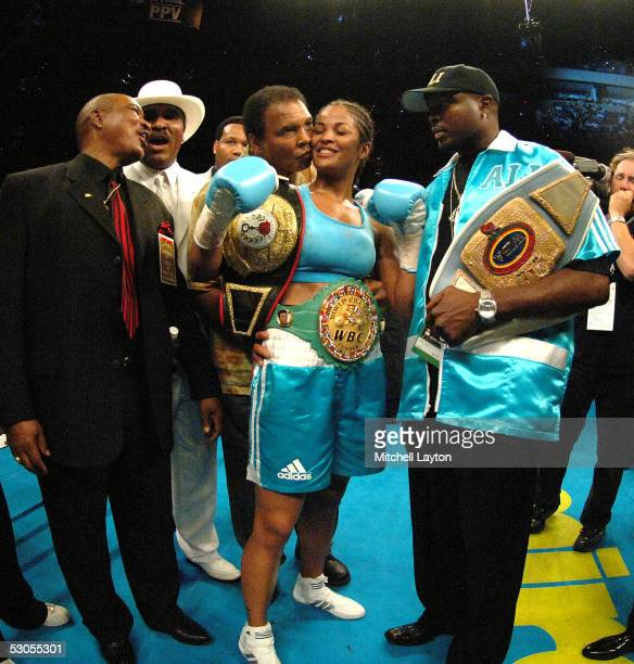 Laila Ali receives a kiss from her father boxing great Muhammad Ali after stopping Erin Toughill in the 2nd round during their fight for the WBC and...