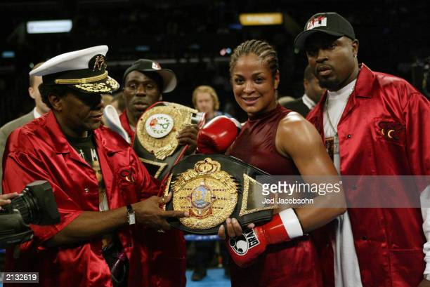 Laila Ali smiles as she holds her IBA title belt with trainer Roger Mayweather after defeating Valerie Mahfood in the women's super middleweight bout...