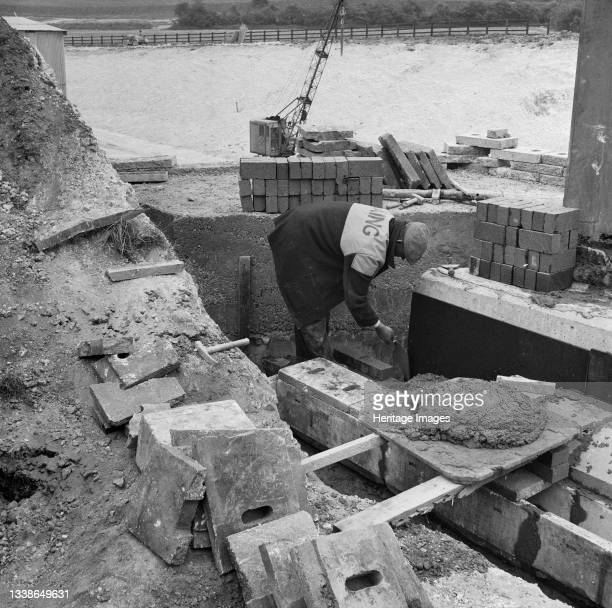Laing labourer laying bricks near a drainage channel during the construction of Structure 9, a bridge carrying the Luton-Dunstable railway line over...