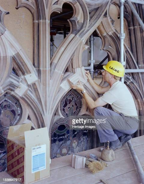 Laing stonemason working on the restoration of the east window at Carlisle Cathedral, positioning a new piece of stone in the tracery using SBD...