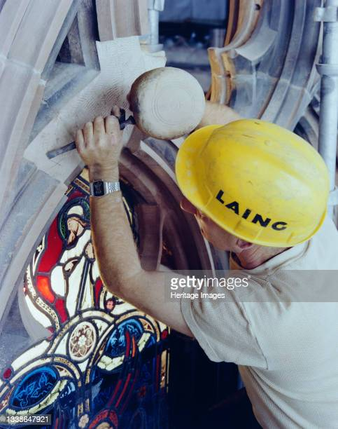 Laing stonemason working on the restoration of the east window at Carlisle Cathedral, chiselling stonework prior to bonding a new piece of stone to...