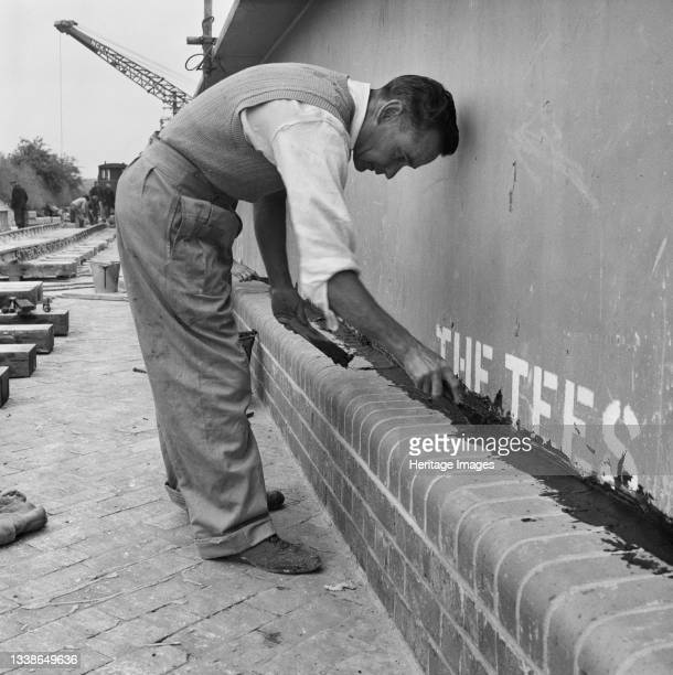 Laing worker applying a bituminous joint sealant between the brickwork and the sides of Structure 9, a bridge carrying the Luton-Dunstable railway...