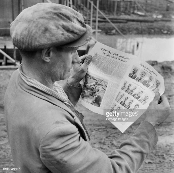 Laing worker on the construction site of the M1, the London to Yorkshire Motorway, reading an article on the motorway in the Company's newsletter,...