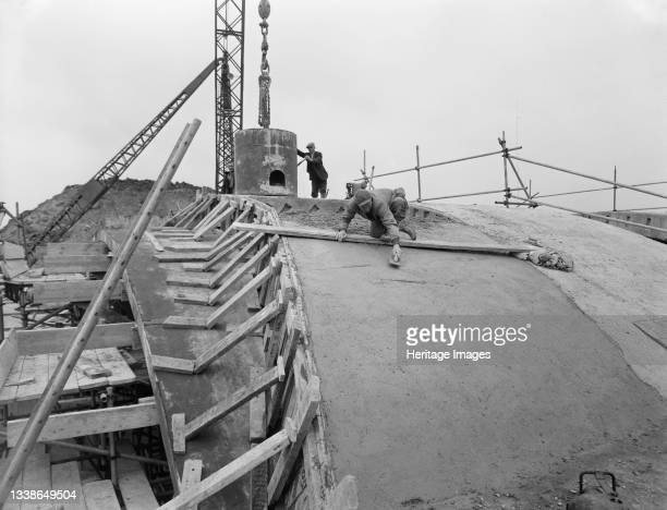 Laing workers constructing the concrete arch of Bridge 52 on the M1, the London to Yorkshire Motorway, at Newport Pagnell. This image was catalogued...