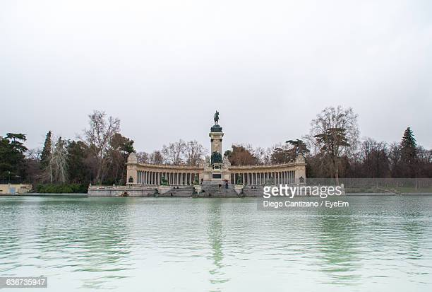 Lake And Alfonso Xii Monument Against Sky