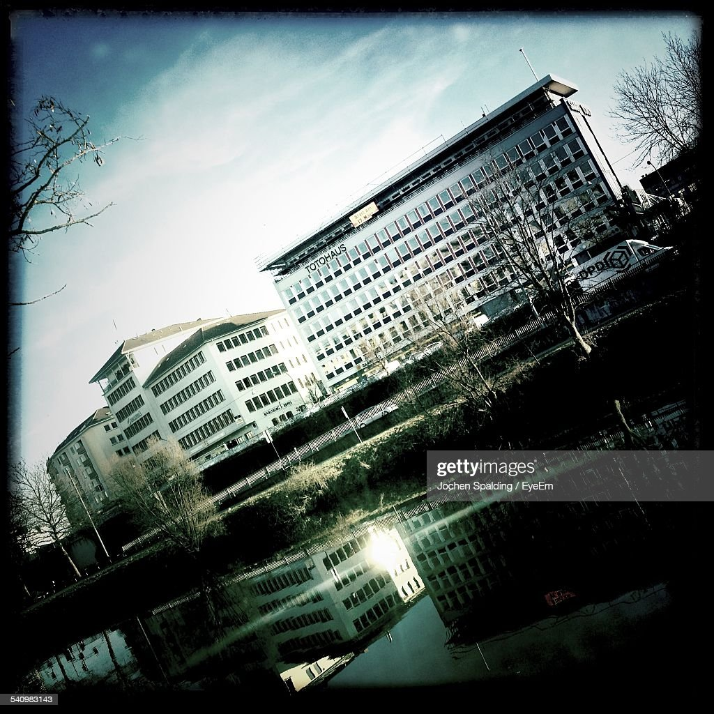 Lake And Buildings Against Cloudy Sky : Stockfoto