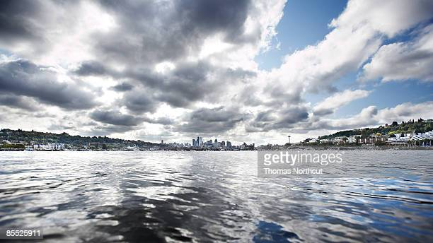 Lake and clouds with cityscape in background