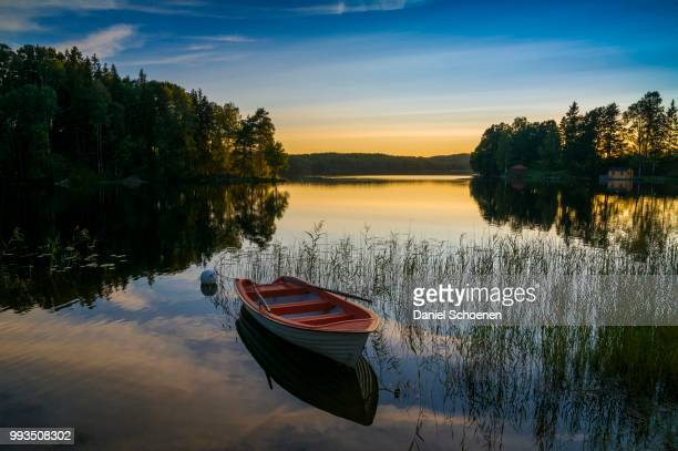 lake and rowing boat at sunset in bengtsfors, dalsland, sweden - dalsland stock photos and pictures