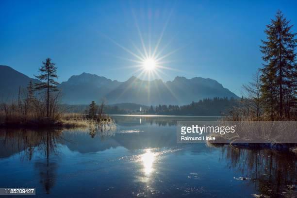 lake barmsee with reflected karwendel mountain range and sun, kruen, krun, upper bavaria, bavaria, germany, europe - krün stock-fotos und bilder