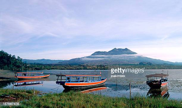 lake batur with boats stationed ashore in bali in indonesia - lake batur stock photos and pictures