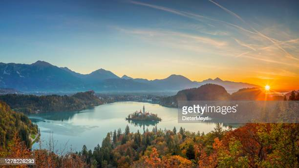meer bled en het eiland met de kerk bij de herfstkleur bij zonsopgang - kapel stockfoto's en -beelden