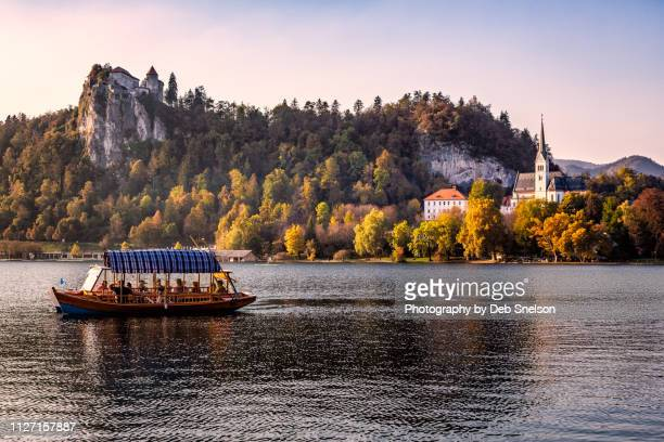 lake bled with pletna and bled castle - slowenien stock-fotos und bilder