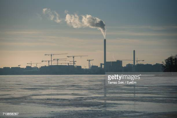 Lake By Factory Emitting Smoke Against Sky During Winter