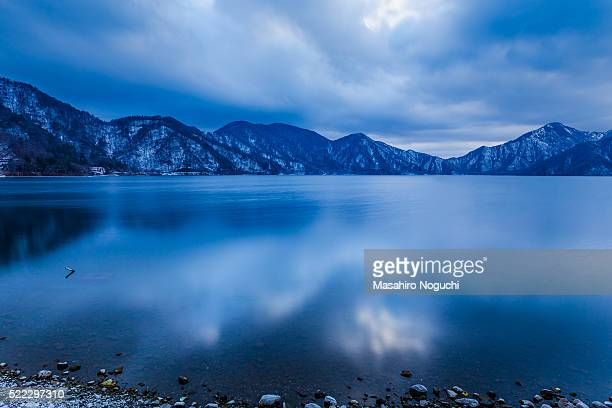 lake chuzenji with snow-capped mountains, late winter evening view - nikko city stock pictures, royalty-free photos & images