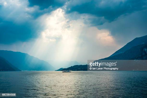 lake como with ferry and dramaric sky, como, lombardy, italy - 雰囲気 ストックフォトと画像