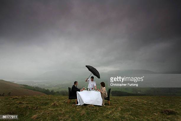 Lake District celebrity chef Peter Sidwell braves the rain as he poses whilst serving up one of his culinary delights to diners Dawn Titley and Dan...
