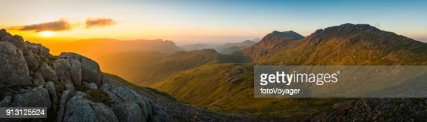 lake district golden sunrise bow fell langdales mountain peaks panorama - english lake district stock photos and pictures